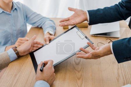 Photo pour Couple de signer le contrat sur presse-papiers avec agent d'assurance à une table en bois - image libre de droit