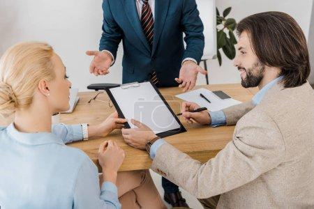 Photo pour Adulte couple signature contrat sur presse-papiers avec agent d'assurance au bureau - image libre de droit
