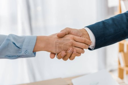 close up of woman and insurance agent shaking hands in office