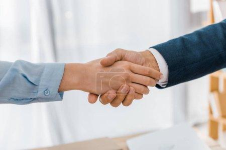 Photo pour Gros plan de la femme et de l'agent d'assurance serrant la main au bureau - image libre de droit