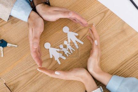 Photo pour Couple faisant cercle avec les mains sur une table en bois avec des gens de papier à l'intérieur - image libre de droit