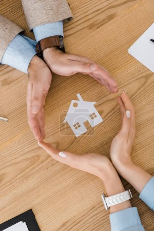 Couple making circle with hands on wooden table with paper house inside, house insurance