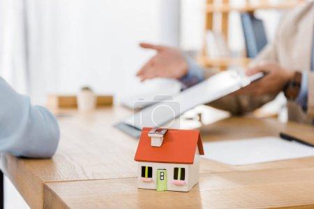 Photo pour Modèle de maison sur table en bois avec des personnes floues à l'arrière-plan - image libre de droit