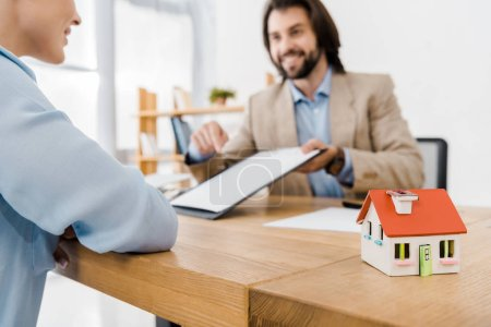 smiling man showing insurance contract to woman with house model on wooden table