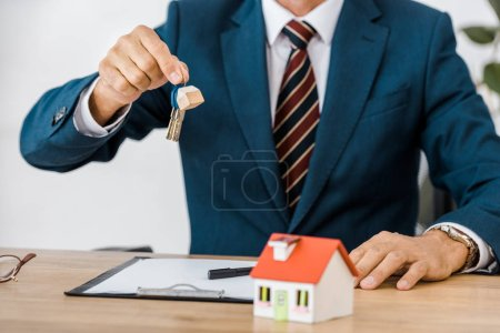 Photo pour Agent d'assurance détenant des clés avec modèle de maison sur la table - image libre de droit
