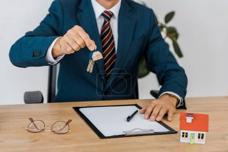 insurance agent holding keys with house model and glasses on table