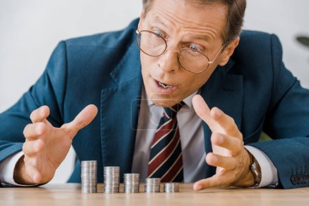 surprised businessman looking at silver coins at wooden table