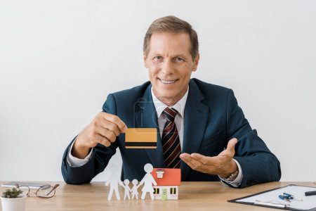 businessman holding credit card with house model and paper cut family on wooden table