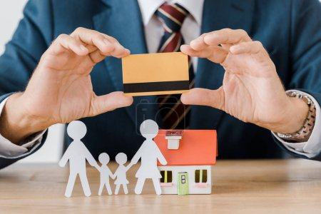 male hands holding credit card with house model and paper cut family on wooden table