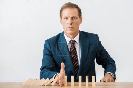 Photo pour Sérieux homme d'affaires avec des blocs jeu de bois dans le bureau, concept d'assurance - image libre de droit