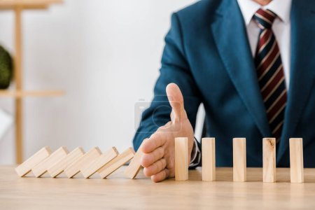 close up of businessman with blocks wood game in office, insurance concept