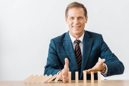 smiling businessman with blocks wood game in office, insurance concept
