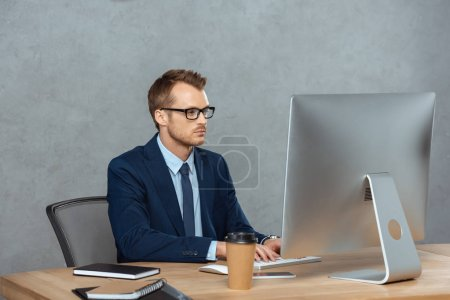 focused businessman in eyeglasses working at table with computer monitor in modern office