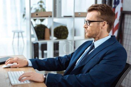 Photo pour Vue latérale du beau businessman dans lunettes travaillant à table avec ordinateur clavier et souris de bureau moderne - image libre de droit