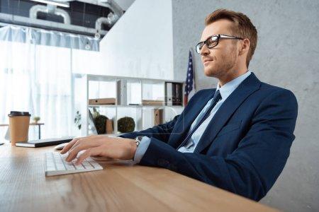 Photo pour Homme d'affaires joyeuse à lunettes en tapant sur le clavier de l'ordinateur à table dans le bureau moderne - image libre de droit