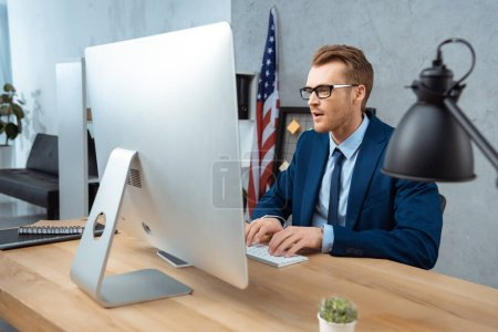 cheerful businessman in eyeglasses working at table with computer monitor in modern office