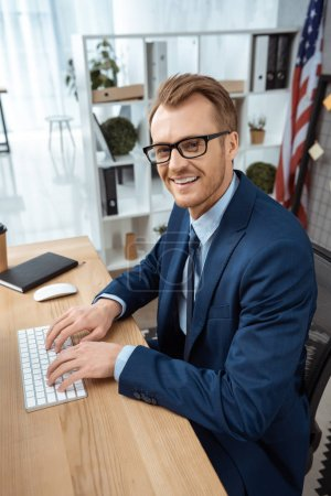 Photo pour Homme d'affaires souriant à lunettes, regardant la caméra et en tapant sur le clavier de l'ordinateur à table dans le bureau moderne - image libre de droit