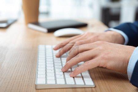Photo pour Cropped image d'homme d'affaires en tapant sur le clavier de l'ordinateur à table dans le bureau moderne - image libre de droit