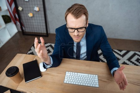 Photo for High angle view of irritated businessman in eyeglasses gesturing by hands at table with computer keyboard and mouse in office - Royalty Free Image