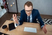 high angle view of irritated businessman in eyeglasses gesturing by hands at table with computer keyboard and mouse in office
