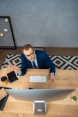 high angle view of young businessman in eyeglasses gesturing by hands at table with computer monitor in office