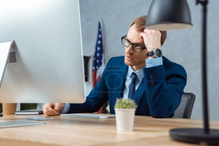 Photo for Tired businessman in eyeglasses working at table with computer monitor in modern office - Royalty Free Image