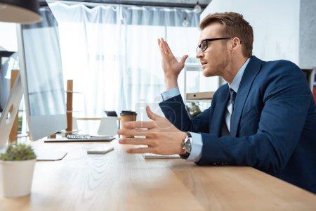 Photo pour Vue latérale du beau businessman dans lunettes gesticulant de mains à table avec moniteur d'ordinateur de bureau - image libre de droit