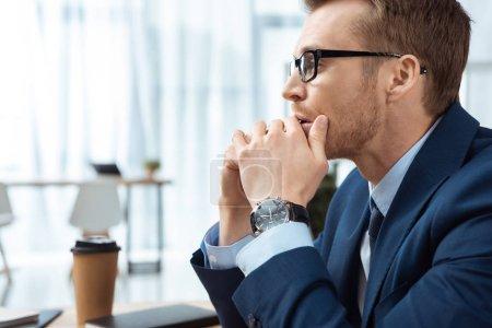 Photo pour Vue de côté de concentré jeune entrepreneur en lunettes de vue dans le bureau moderne - image libre de droit