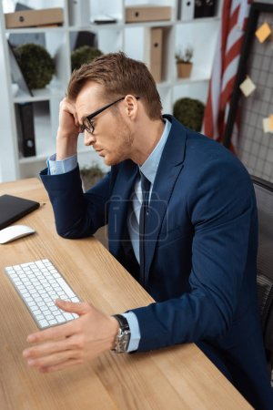 Photo for Tired young businessman in eyeglasses gesturing by hand at table with computer keyboard and mouse in office - Royalty Free Image