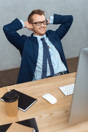 happy young businessman in eyeglasses sitting with hands behind head at table with computer monitor in office