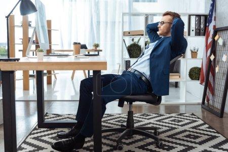 Photo pour Foyer sélectif de l'homme d'affaires dans les lunettes assis avec les mains derrière la tête à la table avec écran d'ordinateur dans le bureau - image libre de droit