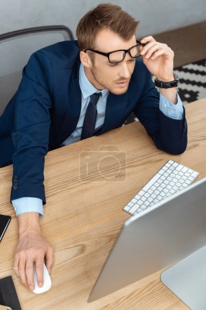 high angle view of focused businessman adjusting eyeglasses and working at table with computer monitor in modern office