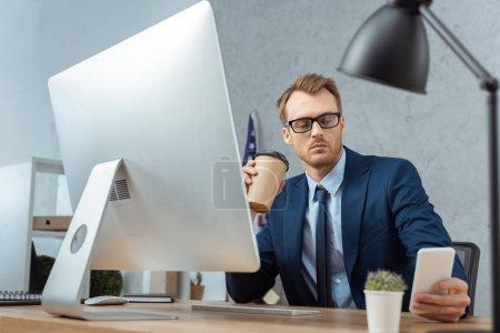 Foto de Hombre de negocios guapo sosteniendo la taza de papel del café y el uso de smartphone en mesa con monitor de la computadora en la oficina moderna - Imagen libre de derechos