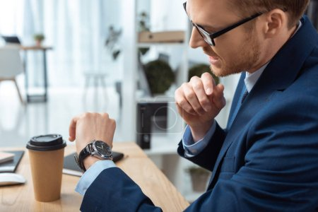 Photo for Selective focus of emotional businessman in eyeglasses checking watch at table with coffee cup in office - Royalty Free Image