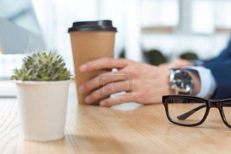Photo pour Image recadrée de l'homme d'affaires assis avec tasse à café jetable à table avec plante en pot et lunettes dans le bureau moderne - image libre de droit