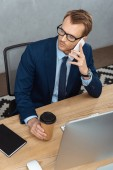 high angle view of businessman in eyeglasses talking on smartphone at table with computer and paper coffee cup in office