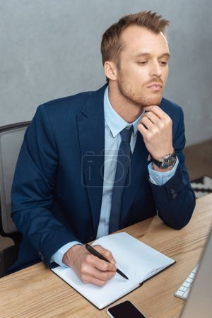 Photo for High angle view of thoughtful businessman writing in textbook at table with smartphone in modern office - Royalty Free Image