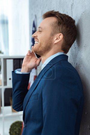 Foto de Vista lateral de feliz hombre de negocios en traje hablando por teléfono inteligente oficina moderna - Imagen libre de derechos