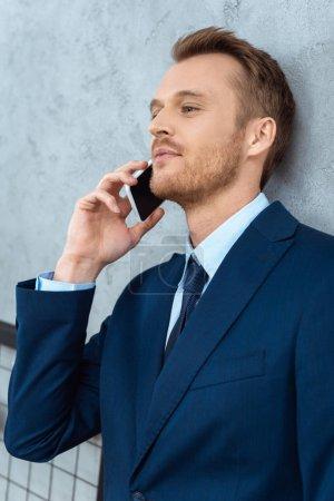 Photo pour Jeune entrepreneur souriant en costume parler sur smartphone dans le bureau moderne - image libre de droit