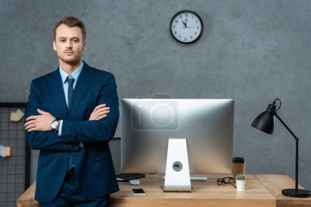 Photo for Handsome businessman standing with crossed arms near table with computer monitor and smartphone in office - Royalty Free Image