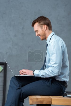 Photo for Side view of smiling young businessman sitting on table and working on laptop in modern office - Royalty Free Image