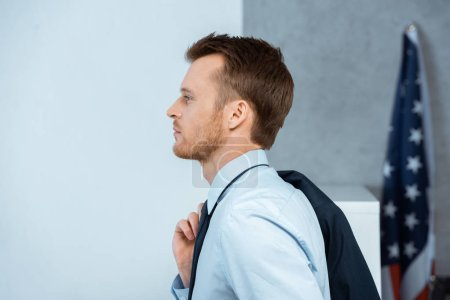 side view of handsome young businessman with jacket over shoulder in office
