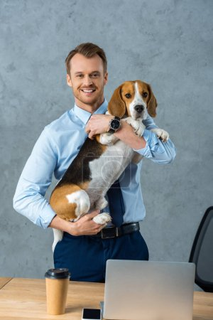 Photo for Cheerful young businessman holding dog near table with smartphone and laptop in modern office - Royalty Free Image