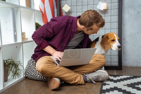 Photo for Young male freelancer with laptop talking to beagle sitting near usa flag in home office - Royalty Free Image