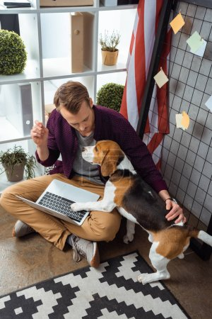 Photo for High angle view of young male freelancer with laptop touching beagle near usa flag in home office - Royalty Free Image