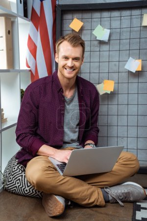 Photo for Smiling handsome male freelancer working on laptop in home office - Royalty Free Image