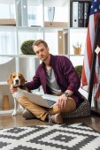 selective focus of male freelancer with laptop touching beagle near usa flag in home office