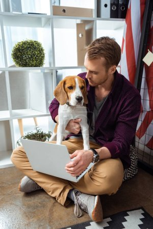 Photo for Male freelancer with laptop holding beagle near usa flag in home office - Royalty Free Image