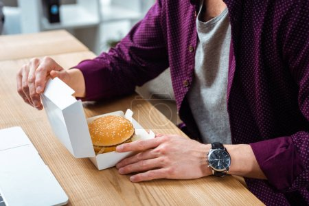 Photo for Partial view of businessman having lunch with burger at table in modern office - Royalty Free Image