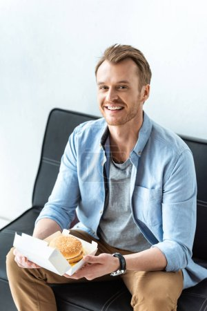 smiling young businessman having lunch with burger while sitting on sofa in office